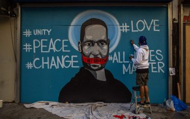 """The artist Celos paints a mural in Downtown Los Angeles on May 30, 2020 in protest against the death of George Floyd, an unarmed black man who died while while being arrested and pinned to the ground by the knee of a Minneapolis police officer. - Clashes broke out and major cities imposed curfews as America began another night of unrest Saturday with angry demonstrators ignoring warnings from President Donald Trump that his government would stop violent protests over police brutality """"cold."""" (Photo by Apu GOMES / AFP) / RESTRICTED TO EDITORIAL USE - MANDATORY MENTION OF THE ARTIST UPON PUBLICATION - TO ILLUSTRATE THE EVENT AS SPECIFIED IN THE CAPTION (Photo by APU GOMES/AFP via Getty Images)"""