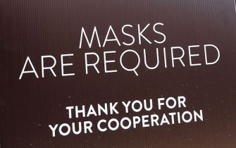 Women wearing facemasks exit a shopping mall where a sign is posted at an entrance reminding people of the mask requirement Westfield Santa Anita shopping mall on June 12, 2020 in Arcadia, California, as Phase 3 in Los Angeles County's battle with the coronavirus pandemic is underway with businesses reopening. (Photo by Frederic J. BROWN / AFP) (Photo by FREDERIC J. BROWN/AFP via Getty Images)