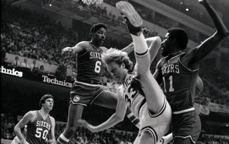 (Original Caption) Celtics' Larry Bird (center) trying to score, does a high leg split as he is hit by 76ers' Caldwell Jones (right), in 1st quarter action of the first game of the NBA semi-final playoffs at Boston Garden (4/18). 76ers' Julius Erving (6) and Steve Mix (50) are also in the photo.