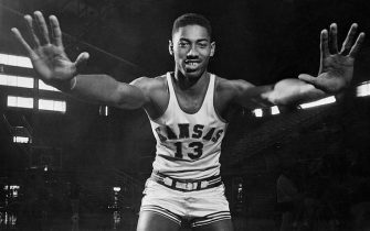 """(Original Caption) Wilt """"The Stilt"""" Chamberlain, 7-foot Kansas Center, displays the mitts which have deflected 127 enemy shots during Kansas' first twenty games this season.Wilt's hands measure 9 1/2 inches from wrist to tip of middle finger and 11 1/2 inches from spread thumb to spread little finger. Thus far Chamberlain has blocked potential of 254 points, or, as Kansas opponents are shooting 35 cents, 88.9 points.Wilt is ranked first nationally in rebounds at 26 per cent,running 3rd nationally in scoring 29.20 average."""