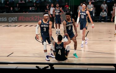 ORLANDO, FL - JULY 27: J.J. Redick #4 is helped up by Josh Hart #3 and Nickiel Alexander-Walker #0 of the New Orleans Pelicans against the Milwaukee Bucks as part of the NBA Restart 2020 on July 27, 2020 at The Arena at ESPN Wide World of Sports Complex in Orlando, Florida. NOTE TO USER: User expressly acknowledges and agrees that, by downloading and/or using this photograph, user is consenting to the terms and conditions of the Getty Images License Agreement.  Mandatory Copyright Notice: Copyright 2020 NBAE (Photo by Jim Poorten/NBAE via Getty Images)