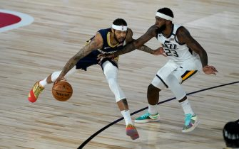 New Orleans Pelicans' Brandon Ingram, left, dribbles around Utah Jazz's Royce O'Neale during the first half of an NBA basketball game Thursday, July 30, 2020, in Lake Buena Vista, Fla. (AP Photo/Ashley Landis, Pool)