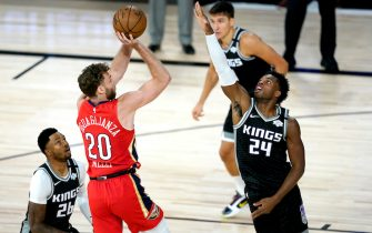 New Orleans Pelicans' Nicolo Melli (20) goes up for a shot against Sacramento Kings' Buddy Hield (24) and Kent Bazemore (26) during the first half of an NBA basketball game Thursday, Aug. 6, 2020 in Lake Buena Vista, Fla. (AP Photo/Ashley Landis, Pool)