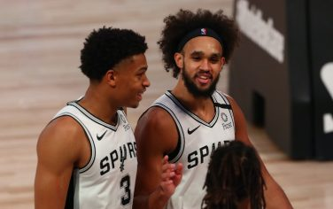 LAKE BUENA VISTA, FLORIDA - AUGUST 05:    San Antonio Spurs guard Patty Mills (foreground) and forward Keldon Johnson #3 and guard Derrick White (middle) talk as the leave the court at halftime on a NBA basketball game against the San Antonio Spurs at HP Field House at ESPN Wide World Of Sports Complex on August 5, 2020 in Lake Buena Vista, Florida. NOTE TO USER: User expressly acknowledges and agrees that, by downloading and or using this photograph, User is consenting to the terms and conditions of the Getty Images License Agreement. (Photo by Kim Klement-Pool/Getty Images)