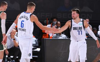 ORLANDO, FL - AUGUST 08: Kristaps Porzingis #6 and Luka Doncic #77 of the Dallas Mavericks shake hands against the Milwaukee Bucks on August 8, 2020 in Orlando, Florida at AdventHealth Arena. NOTE TO USER: User expressly acknowledges and agrees that, by downloading and/or using this photograph, user is consenting to the terms and conditions of the Getty Images License Agreement. Mandatory Copyright Notice: Copyright 2020 NBAE (Photo by Garrett Ellwood/NBAE via Getty Images)