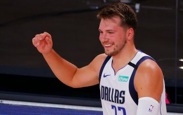 LAKE BUENA VISTA, FLORIDA - AUGUST 08: Luka Doncic #77 of the Dallas Mavericks smiles as he comes off the bench against the Milwaukee Bucks at The Arena at ESPN Wide World Of Sports Complex on August 08, 2020 in Lake Buena Vista, Florida. NOTE TO USER: User expressly acknowledges and agrees that, by downloading and or using this photograph, User is consenting to the terms and conditions of the Getty Images License Agreement. (Photo by Kevin C. Cox/Getty Images)