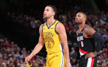 PORTLAND, OR - FEBRUARY 13: Stephen Curry #30 of the Golden State Warriors and Damian Lillard #0 of the Portland Trail Blazers look on during the game on February 13, 2019 at the Moda Center in Portland, Oregon. NOTE TO USER: User expressly acknowledges and agrees that, by downloading and/or using this photograph, user is consenting to the terms and conditions of the Getty Images License Agreement. Mandatory Copyright Notice: Copyright 2019 NBAE (Photo by Sam Forencich/NBAE via Getty Images)