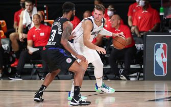 ORLANDO, FL - AUGUST 17: Luka Doncic #77 of the Dallas Mavericks handles the ball against Marcus Morris Sr. #31 of the LA Clippers during Round One, Game One of the NBA Playoffs on August 17, 2020 at AdventHealth Arena in Orlando, Florida. NOTE TO USER: User expressly acknowledges and agrees that, by downloading and/or using this Photograph, user is consenting to the terms and conditions of the Getty Images License Agreement. Mandatory Copyright Notice: Copyright 2020 NBAE (Photo by Joe Murphy/NBAE via Getty Images)