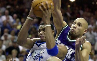 ORLANDO, UNITED STATES:  Orlando Magic forward Tracy McGrady(L) drives between Milwaukee Bucks guard Sam Cassell (lower) and Bucks forwad Glenn Robinson(R) for two points during the overtime of the third game of the first round NBA playoff at the TD Waterhouse Centre in Orlando, FL. 28 April 2001. AFP PHOTO/Tony RANZE (Photo credit should read TONY RANZE/AFP via Getty Images)