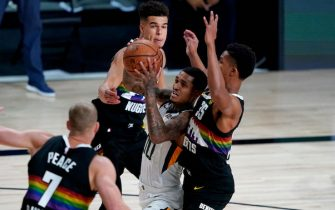 Utah Jazz's Jordan Clarkson (00) tries to shoot as Denver Nuggets' PJ Dozier (35) defends during the first half of an NBA basketball first round playoff game, Monday, Aug. 3, 2020, in Lake Buena Vista, Fla.(AP Photo/Ashley Landis, Pool)