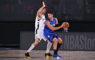 ORLANDO, FL - AUGUST 20: Nikola Vucevic #9 of the Orlando Magic handles the ball against Robin Lopez #42 of the Milwaukee Bucks during Round One, Game Two of the NBA Playoffs on August 20, 2020 at the The Field House at ESPN Wide World Of Sports Complex in Orlando, Florida. NOTE TO USER: User expressly acknowledges and agrees that, by downloading and/or using this Photograph, user is consenting to the terms and conditions of the Getty Images License Agreement. Mandatory Copyright Notice: Copyright 2020 NBAE (Photo by Garrett Ellwood/NBAE via Getty Images)