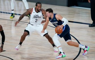 LAKE BUENA VISTA, FLORIDA - AUGUST 23: Dallas Mavericks' Luka Doncic #77 drives toward the basket as Los Angeles Clippers' Kawhi Leonard #2 defends  during the first half of an NBA basketball first round playoff game  at AdventHealth Arena at ESPN Wide World Of Sports Complex on August 23, 2020 in Lake Buena Vista, Florida. NOTE TO USER: User expressly acknowledges and agrees that, by downloading and or using this photograph, User is consenting to the terms and conditions of the Getty Images License Agreement.  (Photo by Ashley Landis-Pool/Getty Images)