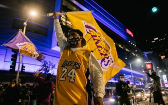 LOS ANGELES, CA - OCTOBER 11: A Lakers fan walks with a Lakers flag in front of the Staples Center on October 11, 2020 in Los Angeles, California. People gathered to celebrate after the Los Angeles Lakers defeated the Miami Heat in Game 6 of the NBA Finals. (Photo by Brandon Bell/Getty Images)