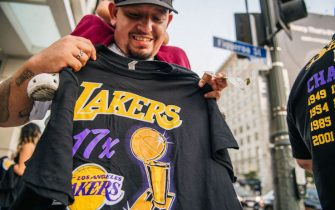 LOS ANGELES, CA - OCTOBER 11: A man sells buys a Lakers shirt outside of the Staples Center on October 11, 2020 in Los Angeles, California. People gathered to celebrate after the Los Angeles Lakers defeated the Miami Heat in game 6 of the NBA finals. (Photo by Brandon Bell/Getty Images)