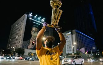LOS ANGELES, CA - OCTOBER 11: A Lakers fan hoists a replica of the Larry O'Brien trophy near the Staples Center on October 11, 2020 in Los Angeles, California. People gathered to celebrate after the Los Angeles Lakers defeated the Miami Heat in game 6 of the NBA finals. (Photo by Brandon Bell/Getty Images)