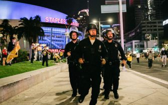 LOS ANGELES, CA - OCTOBER 11: Law enforcement officers prepare to disperse a crowd of Lakers fans near the Staples Center on October 11, 2020 in Los Angeles, California. People gathered to celebrate after the Los Angeles Lakers defeated the Miami Heat in Game 6 of the NBA Finals. (Photo by Brandon Bell/Getty Images)