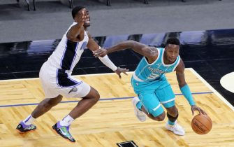 ORLANDO, FL - DECEMBER 17:  Terry Rozier #3 of the Charlotte Hornets slips past Dwayne Bacon #8 of the Orlando Magic at Amway Center on December 17, 2020 in Orlando, Florida. NOTE TO USER: User expressly acknowledges and agrees that, by downloading and or using this photograph, User is consenting to the terms and conditions of the Getty Images License Agreement. (Photo by Alex Menendez/Getty Images)