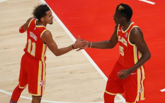 ATLANTA, GEORGIA - DECEMBER 28:  Trae Young #11 of the Atlanta Hawks reacts with Clint Capela #15 during the first half against the Detroit Pistons at State Farm Arena on December 28, 2020 in Atlanta, Georgia.  NOTE TO USER: User expressly acknowledges and agrees that, by downloading and or using this photograph, User is consenting to the terms and conditions of the Getty Images License Agreement. (Photo by Kevin C. Cox/Getty Images)