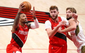 PORTLAND, OREGON - JANUARY 14: Damian Lillard #0 takes a shot alongside Jusuf Nurkic #27 of the Portland Trail Blazers and Domantas Sabonis #11 of the Indiana Pacers in the third quarter at Moda Center on January 14, 2021 in Portland, Oregon. NOTE TO USER: User expressly acknowledges and agrees that, by downloading and or using this photograph, User is consenting to the terms and conditions of the Getty Images License Agreement. (Photo by Abbie Parr/Getty Images)