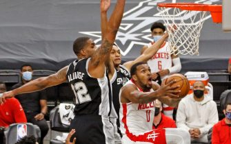 SAN ANTONIO, TX - JANUARY 14:  Sterling Brown #0 of the Houston Rockets drives past LaMarcus Aldridge #12 of the San Antonio Spurs at AT&T Center on January 14, 2021 in San Antonio, Texas.  NOTE TO USER: User expressly acknowledges and agrees that , by downloading and or using this photograph, User is consenting to the terms and conditions of the Getty Images License Agreement. (Photo by Ronald Cortes/Getty Images)