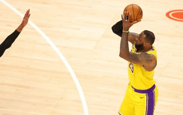 ATLANTA, GEORGIA - FEBRUARY 01:  LeBron James #23 of the Los Angeles Lakers shoots a three-point basket against Cam Reddish #22 of the Atlanta Hawks during the second half at State Farm Arena on February 01, 2021 in Atlanta, Georgia.  NOTE TO USER: User expressly acknowledges and agrees that, by downloading and or using this photograph, User is consenting to the terms and conditions of the Getty Images License Agreement.  (Photo by Kevin C. Cox/Getty Images)