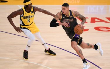 LOS ANGELES, CALIFORNIA - MARCH 12: Kyle Kuzma #0 of the Los Angeles Lakers drives to the basket on Justin Holiday #8 of the Indiana Pacers during the first quarter at Staples Center on March 12, 2021 in Los Angeles, California. (Photo by Harry How/Getty Images)  NOTE TO USER: User expressly acknowledges and agrees that, by downloading and/or using this Photograph, user is consenting to the terms and conditions of the Getty Images License Agreement. Mandatory Copyright Notice: Copyright 2021 NBAE.
