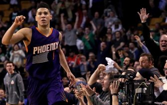 BOSTON - MARCH 24: An off-balance three pointer by Phoenix Suns guard Devin Booker (1) brings the Garden fans to their feet and Booker signals it's good for 3 of his 70 points on the night. The Boston Celtics host the Phoenix Suns at TD Garden in Boston on Mar. 24, 2017. (Photo by Barry Chin/The Boston Globe via Getty Images)