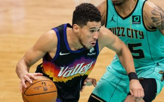 CHARLOTTE, NORTH CAROLINA - MARCH 28: Devin Booker #1 of the Phoenix Suns drives to the basket while guarded by P.J. Washington #25 of the Charlotte Hornets during the third quarter during their game at Spectrum Center on March 28, 2021 in Charlotte, North Carolina. NOTE TO USER: User expressly acknowledges and agrees that, by downloading and or using this photograph, User is consenting to the terms and conditions of the Getty Images License Agreement. (Photo by Jacob Kupferman/Getty Images)