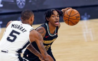 SAN ANTONIO, TX - JANUARY 30:  Ja Morant #12 of the Memphis Grizzlies drives by Dejounte Murray #5 of the San Antonio Spurs at AT&T Center on January 30, 2021 in San Antonio, Texas.  NOTE TO USER: User expressly acknowledges and agrees that , by downloading and or using this photograph, User is consenting to the terms and conditions of the Getty Images License Agreement. (Photo by Ronald Cortes/Getty Images)