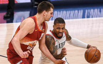 """DENVER, CO - FEBRUARY 23: Nikola Jokic (15) of the Denver Nuggets locks down Damian Lillard (0) of the Portland Trail Blazers on the perimeter during the fourth quarter of Denver""""u2019s 11-106 win at Ball Arena on Tuesday, February 23, 2021. (Photo by AAron Ontiveroz/MediaNews Group/The Denver Post via Getty Images)"""