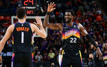 PHOENIX, AZ - JUNE 1:  Devin Booker #1 and Deandre Ayton #22 of the Phoenix Suns high five during Round 1, Game 5 of the 2021 NBA Playoffs on June 1, 2021 at Phoenix Suns Arena in Phoenix, Arizona. NOTE TO USER: User expressly acknowledges and agrees that, by downloading and or using this photograph, user is consenting to the terms and conditions of the Getty Images License Agreement. Mandatory Copyright Notice: Copyright 2021 NBAE (Photo by Michael Gonzales/NBAE via Getty Images)