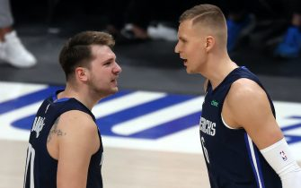 DALLAS, TEXAS - MAY 28:  Luka Doncic #77 and Kristaps Porzingis #6 of the Dallas Mavericks react against the LA Clippers in the first quarter in game three of the Western Conference first round series at American Airlines Center on May 28, 2021 in Dallas, Texas.  NOTE TO USER: User expressly acknowledges and agrees that, by downloading and or using this photograph, User is consenting to the terms and conditions of the Getty Images License Agreement. (Photo by Ronald Martinez/Getty Images)
