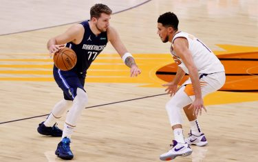 PHOENIX, ARIZONA - DECEMBER 23: Luka Doncic #77 of the Dallas Mavericks controls the ball against Devin Booker #1 of the Phoenix Suns during the NBA game at PHX Arena on December 23, 2020 in Phoenix, Arizona.  The Suns defeated the Mavericks 106-102.  NOTE TO USER: User expressly acknowledges and agrees that, by downloading and/or using this Photograph, user is consenting to the terms and conditions of the Getty Images License Agreement. (Photo by Christian Petersen/Getty Images)