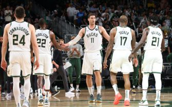 MILWAUKEE, WI - JULY 1: Brook Lopez #11 hi-fives Khris Middleton #22, P.J. Tucker #17, Pat Connaughton #24 and Jrue Holiday #21 of the Milwaukee Bucks during Game 5 of the Eastern Conference Finals of the 2021 NBA Playoffs on July 1, 2021 at the Fiserv Forum Center in Milwaukee, Wisconsin. NOTE TO USER: User expressly acknowledges and agrees that, by downloading and or using this Photograph, user is consenting to the terms and conditions of the Getty Images License Agreement. Mandatory Copyright Notice: Copyright 2021 NBAE (Photo by Gary Dineen/NBAE via Getty Images).