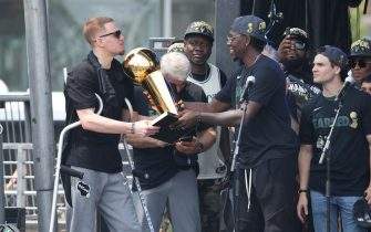MILWAUKEE, WI - JULY 22: Jrue Holiday #21 of the Milwaukee Buck gives Donte DiVincenzo #0 the Larry O'Brien Trophy during their Victory Parade & Rally of the 2021 NBA Finals on July 22, 2021 at the Fiserv Forum in Milwaukee, Wisconsin. NOTE TO USER: User expressly acknowledges and agrees that, by downloading and or using this Photograph, user is consenting to the terms and conditions of the Getty Images License Agreement. Mandatory Copyright Notice: Copyright 2021 NBAE (Photo by Mike E. Roemer/NBAE via Getty Images).