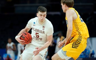 INDIANAPOLIS, INDIANA - MARCH 20: Balsa Koprivica #5 of the Florida State Seminoles handles the ball against Hayden Koval #25 of the UNC-Greensboro Spartans during the first half in the first round game of the 2021 NCAA Men's Basketball Tournament at Bankers Life Fieldhouse on March 20, 2021 in Indianapolis, Indiana. (Photo by Sarah Stier/Getty Images)
