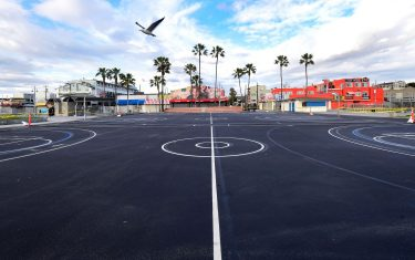 TOPSHOT - A bird flies over a closed basketball court at Venice Beach on April 10, 2020 in Los Angeles, California, where the Stay-At-Home order has been extended from April 19 to May 15 amid the coronavirus pandemic. (Photo by Frederic J. BROWN / AFP) (Photo by FREDERIC J. BROWN/AFP via Getty Images)