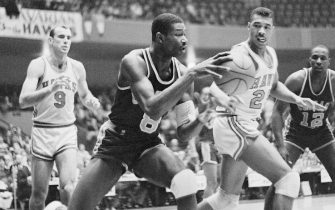(Original Caption) Chicago Packers Wally Bellamy, (#8) charges toward his end of the court after retrieving the ball from Hawks Bob Pettit, (#9), in the first quarter action here. Hawk Shellie McMillon, (#25) made an unsuccessful try for the ball. Packer Andy Johnson, (#12) is shown in the background.