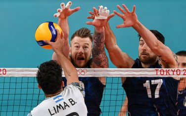 (L-R) Argentina's Bruno Lima hits the ball in front of Italy's Ivan Zaytsev and Simone Anzani in the men's quarter-final volleyball match between Italy and Argentina during the Tokyo 2020 Olympic Games at Ariake Arena in Tokyo on August 3, 2021. (Photo by YURI CORTEZ / AFP) (Photo by YURI CORTEZ/AFP via Getty Images)