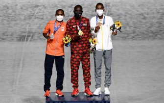 (From L) Second-placed Netherlands' Abdi Nageeye, first-placed Kenya's Eliud Kipchoge and Belgium's Bashir Abdi celebrate on the podium during the victory ceremony of the men's marathon event as part of the closing ceremony of the Tokyo 2020 Olympic Games at the Olympic Stadium in Tokyo on August 8, 2021. (Photo by Jewel SAMAD / AFP) (Photo by JEWEL SAMAD/AFP via Getty Images)