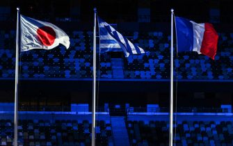TOPSHOT - (L to R) The Japanese, Greek and French flags are pictured during the closing ceremony of the Tokyo 2020 Olympic Games, at the Olympic Stadium, in Tokyo, on August 8, 2021. (Photo by Adek BERRY / AFP) (Photo by ADEK BERRY/AFP via Getty Images)