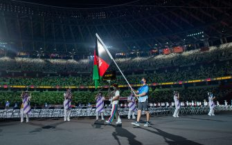 Handout photo dated 24/08/2021 provided by OIS of a Paralympic volunteer carrying the national flag of Afghanistan during the opening ceremony of the Tokyo 2020 Paralympic Games at Olympic Stadium in Japan. Picture date: Tuesday August 24, 2021.