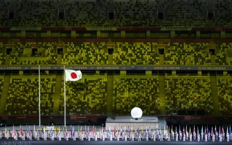 Handout photo dated 24/08/2021 provided by OIS of Athlete's Parade Assistants holding flags of the competing countries in front of the Protocol Stage during the opening ceremony of the Tokyo 2020 Paralympic Games at Olympic Stadium in Japan. Picture date: Tuesday August 24, 2021.