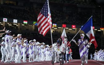 epa09449206 A handout photo made available by OIS/IOC shows Flag Bearer Matt Scott USA carrying his national flag ahead of Flag Bearer Alexandre Leaute FRA in the Olympic Stadium during the Closing Ceremony for the Tokyo 2020 Paralympic Games, Tokyo, Japan, Sunday 05 September 2021.  EPA/Thomas Lovelock for OIS HANDOUT   EDITORIAL USE ONLY/NO SALES