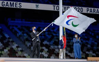 epa09449205 A handout photo made available by OIS/IOC shows Andrew Parsons, president of the International Paralympic Committee waving the Paralympic flag before handing it to Anne Hidalgo, Mayor of Paris during the Closing Ceremony for the Tokyo 2020 Paralympic Games, Tokyo, Japan, Sunday 05 September 2021.  EPA/Thomas Lovelock for OIS HANDOUT   EDITORIAL USE ONLY/NO SALES