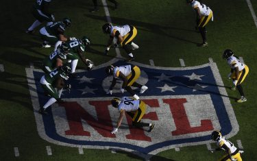 EAST RUTHERFORD, NEW JERSEY - DECEMBER 22: The New York Jets ready at the line of scrimmage over the NFL logo during the first half of the game against the Pittsburgh Steelers at MetLife Stadium on December 22, 2019 in East Rutherford, New Jersey. (Photo by Sarah Stier/Getty Images)