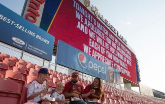 SANDY, UT -  AUGUST 26: Fans finish their dinner as the digital scoreboard above them alerts that the game between Real Salt Lake and the Los Angeles FC was postponed at Rio Tinto Stadium on August 26, 2020 in Sandy, Utah. Several sporting leagues across the nation today are postponing their schedules as players protest the shooting of Jacob Blake by Kenosha, Wisconsin police. (Photo by Chris Gardner/Getty Images)