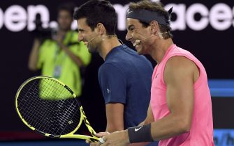 Novak Djokovic of Serbia (L) and Rafael Nadal of Spain (R) share a lighter moment as they and other top players play in the Rally for Relief charity tennis match in support of the victims of the Australian bushfires, in Melbourne of January 15, 2020, ahead of the Australian Open tennis tournament. (Photo by WILLIAM WEST / AFP) / -- IMAGE RESTRICTED TO EDITORIAL USE - STRICTLY NO COMMERCIAL USE -- (Photo by WILLIAM WEST/AFP via Getty Images)