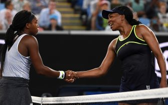 MELBOURNE, AUSTRALIA - JANUARY 20: Coco Gauff of the United States of America and Venus Williams of the United States of America embrace at the net following their Women's Singles first round match on day one of the 2020 Australian Open at Melbourne Park on January 20, 2020 in Melbourne, Australia. (Photo by Hannah Peters/Getty Images)