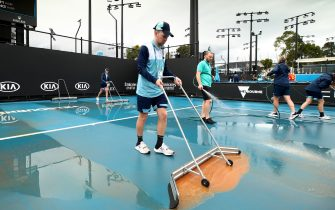 MELBOURNE, AUSTRALIA - JANUARY 23: (EDITORS NOTE: A graduated grey filter was used to create this image.) Staff are seen attempting to clean dirt off the outside courts after being caused by rainfall on day four of the 2020 Australian Open at Melbourne Park on January 23, 2020 in Melbourne, Australia. (Photo by Clive Brunskill/Getty Images)